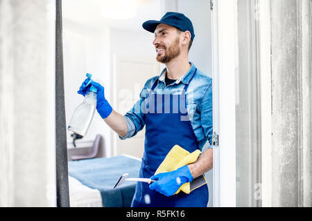 Man as a professional cleaner in blue uniform washing window with cotton wiper indoors - Stock Photo