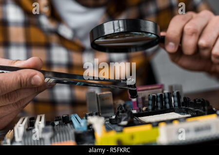 cropped shot of computer engineer with tweezers and magnifying glass repairing motherboard - Stock Photo