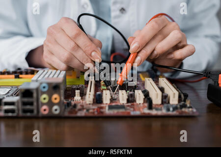 cropped shot of computer engineer with tester examining motherboard - Stock Photo
