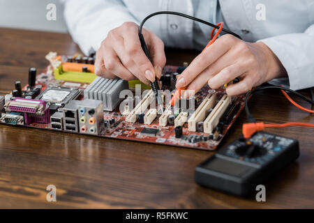 cropped shot of electric engineer with tester examining computer motherboard - Stock Photo