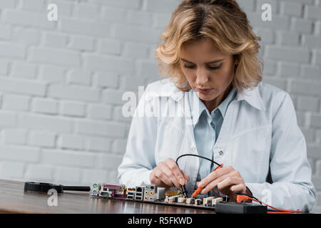 female electronic engineer with tester examining computer motherboard - Stock Photo