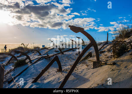 Tourist woman at Cemetery of Anchors. Memorial monument to dead fishermen of tuna industry in Portugal. Barril beach, Santa Luzia, Algarve - Stock Photo