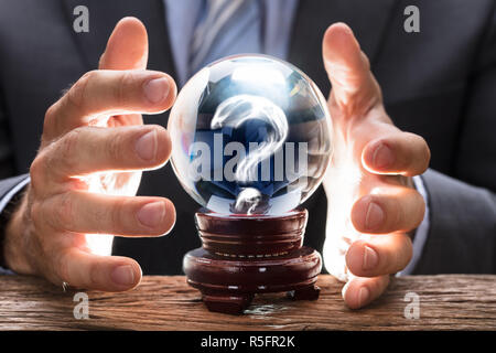 Businessman Covering Crystal Ball With Question Mark - Stock Photo