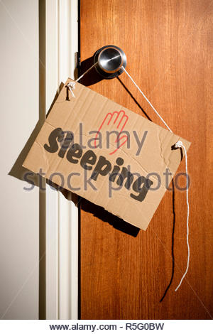 Sleeping written on a makeshift sign hanging on the door handle, Dorset, England - Stock Photo