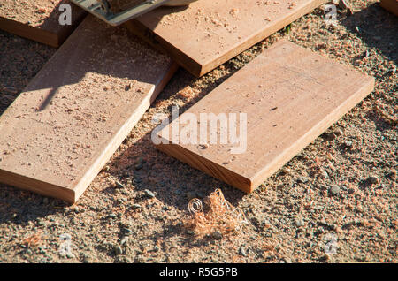 Offcuts of wood piled on the ground in the sun during home renovations - Stock Photo
