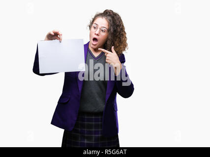 Young brunette student girl wearing school uniform holding blank paper over isolated background very happy pointing with hand and finger - Stock Photo