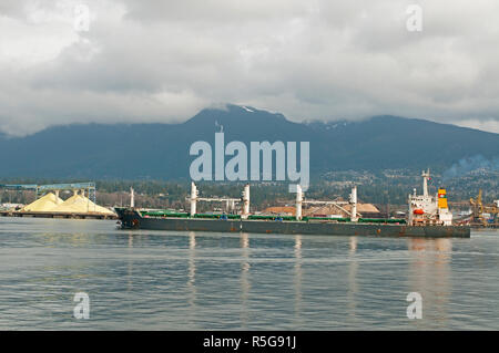 The Bulk Carrier vessel in the process of departing from Vancouver in British Columbia. - Stock Photo