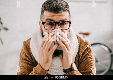 portrait of sick man in knitted scarf sitting in office, sneezing and covering mouth with tissue - Stock Photo