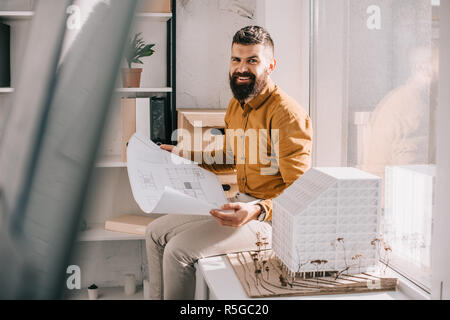 smiling bearded adult male architect sitting near house model, holding blueprint and working on project in office - Stock Photo