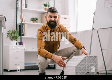smiling bearded adult male architect looking at camera and presenting house model in office - Stock Photo
