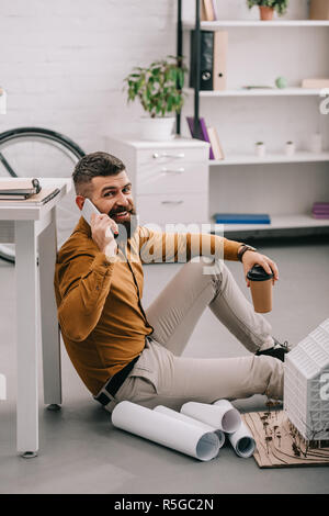smiling bearded adult male architect talking on smartphone, holding coffee to go and working on blueprints in office - Stock Photo
