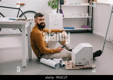 smiling bearded adult male architect using smartphone, holding coffee to go and working on blueprints in office - Stock Photo