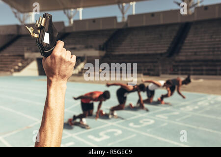 Close up of hand firing a starting pistol to start a race. Athletes taking off from starting block on a running track at the start of a race. - Stock Photo