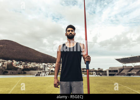 Athlete standing in a track and field stadium holding a javelin. Athlete training in javelin throw standing in a ground. - Stock Photo