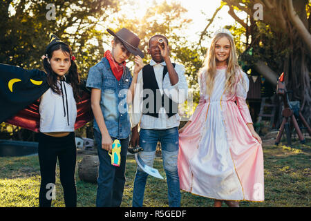 Group of kids standing in backyard garden wearing different costume. Young boys and girls having fun outdoors with superhero costumes. - Stock Photo