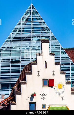 Traditional gabled house in the old town, glass and steel Pyramid of the new city library Ulm, - Stock Photo