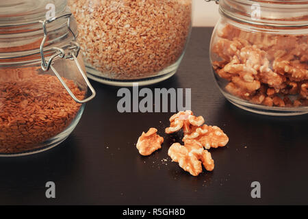 Healthy food, nuts, linseed and oats in glass jars - Stock Photo