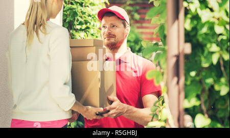 woman accepting a home delivery of boxes from deliveryman. copy space - Stock Photo