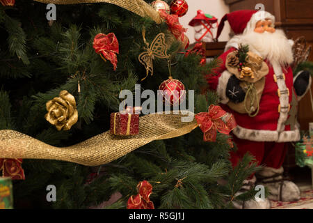 close up christmas tree with santa claus in the background - Stock Photo