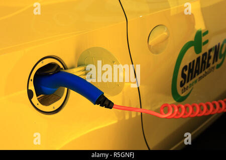 Electric car at the charging station with charging cable, Electric car sharing service, Milan, Italy - Stock Photo
