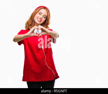 Young beautiful hipster woman over isolated background wearing headphones and cap smiling in love showing heart symbol and shape with hands. Romantic  - Stock Photo