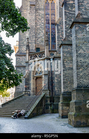 Two unrecognizable homeless men sleep in the shadows on the bottom steps of staircase of Gothic cathedral in old center of Prague, Czech Republic - Stock Photo