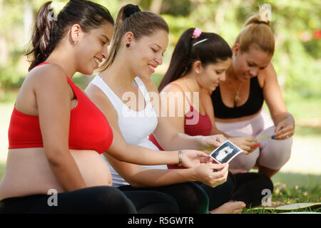 Pregnant Women Sharing Ecography Images In Prenatal Class