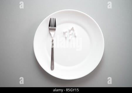 white tablet pill medical drug on plate with fork for food and health gray background - Stock Photo