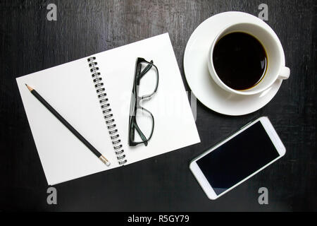 Top view of office desk workspace with coffee cup, notebook, pencil ,mobile phone ,glasses on wooden background - Stock Photo