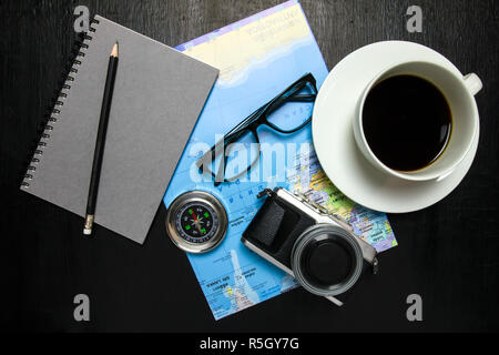 Top view of office desk workspace with coffee cup, camera ,world map ,compass,notebook,pencil ,glasses on wooden background - Stock Photo