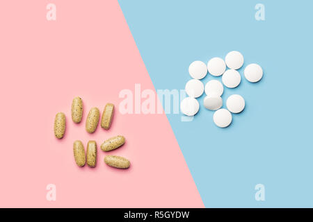 A pile of white pills and a pile of yellow vitamins on bright blue and pink background shot with studio light from above - Stock Photo