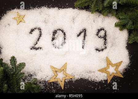 2019 written in snow on black background decorated with green branches and golden stars - Stock Photo