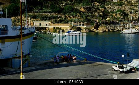 Mgarr harbour, Gozo - 8th October 2018:Tourists in the harbour of Mgarr - Stock Photo