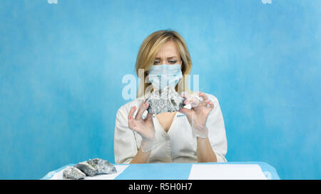 A woman lab worker examines stones for anilization, the content of harmful asbestos. - Stock Photo