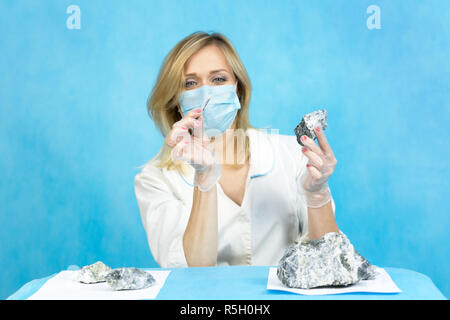 A woman lab worker examines the stones with tweezers takes the fibers of harmful asbestos. - Stock Photo