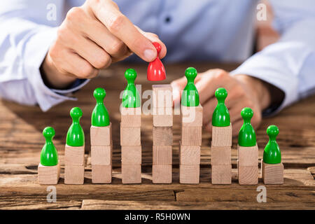 Person Placing Red Figure On Stacked Blocks - Stock Photo