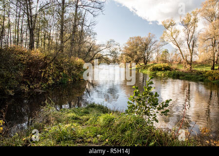 Olse and Stonvaka river tributary in Karvina city in Czech republic with trees around and blue sky with clouds during nice autumn day - Stock Photo