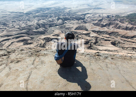 Man on top of Layer Volcanic ash as sand ground of Mount Bromo volcano (Gunung Bromo) at Bromo Tengger Semeru National Park, East Java, Indonesia - Stock Photo