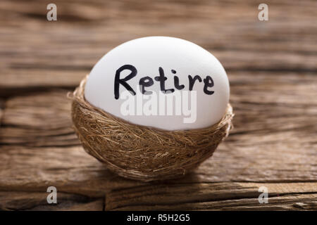 Retire Written On White Egg In Nest - Stock Photo