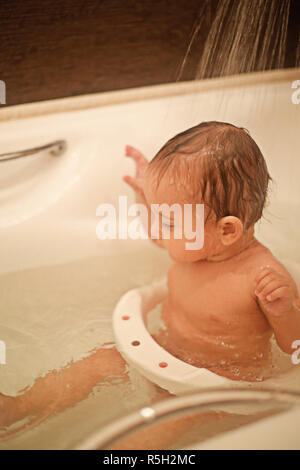 Seven-month-old beautiful baby bathes in the bathroom - Stock Photo