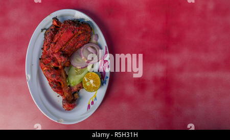 Authentic Indian - Malaysian food from family street restaurant. Spicy Tandoori chicken plate isolated on red background. Delicious - Stock Photo