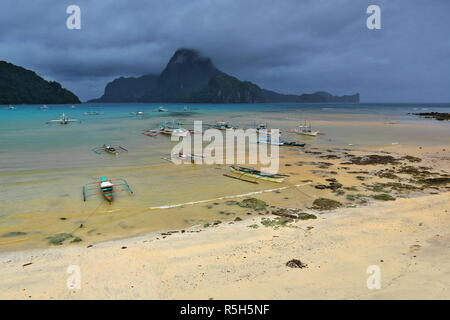 Fishing and tour boats stranded and moored at the beach in a rainy morning preventing them from going out to sea to carry out their usual tasks-fishin - Stock Photo