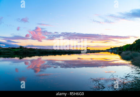 Stunning sunrise and reflection on calm arm leading to Ruataniwha Inlet Collingwood, South Island New Zealand - Stock Photo