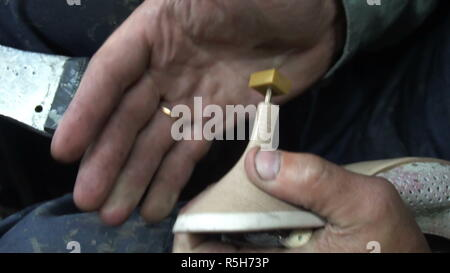 the shoemaker at work.The process of repairing shoes in workshop - Stock Photo