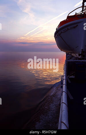 lifeboat on a ship in the sunset. lifeboat on a passport - Stock Photo