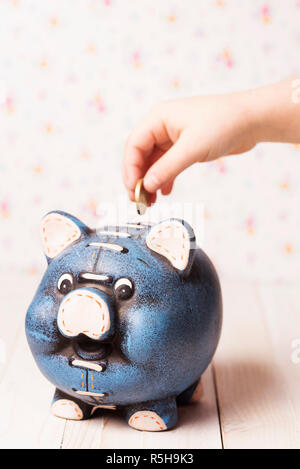 Little child depositing money into a piggy bank. - Stock Photo
