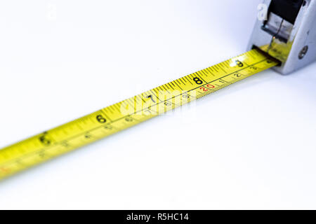 Tape measure closeup with out of focus elements on a white background - Stock Photo