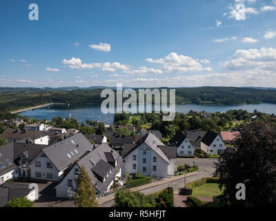 Panoramic view over the lake Sorpesee with some sailing boats and sone houses of Langscheid in Sauerland, Germany in the front - Stock Photo