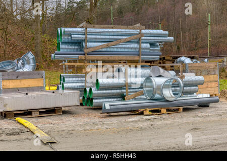 FLODA, SWEDEN - NOVEMBER 21 2018: Many new shiny corrugated sheet iron metal tubes stored on shelves on construction site ahead of being used - Stock Photo