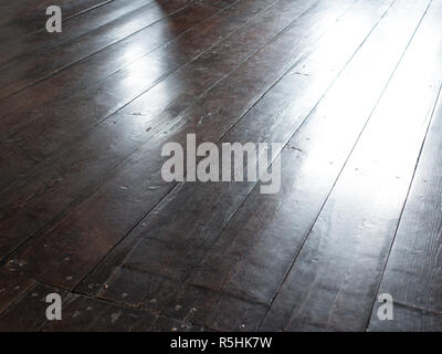 Dark wooden flor perspective view with light point in center - Stock Photo